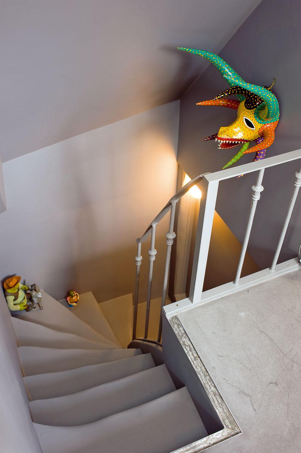 Na neutrálnom sivom schodisku pestrofarebné doplnky len jemne naznačujú, že stúpate do podkrovia plného živých farieb. Privedie vás do pracovne, ktorá vznikla vpriestore na rozhraní dennej anočnej časti bytu. Schodisko lemujú vstavané skrine, na mieru zasadené pod šikminy strechy – vtomto podkroví sa využil naozaj každý kubický centimeter.