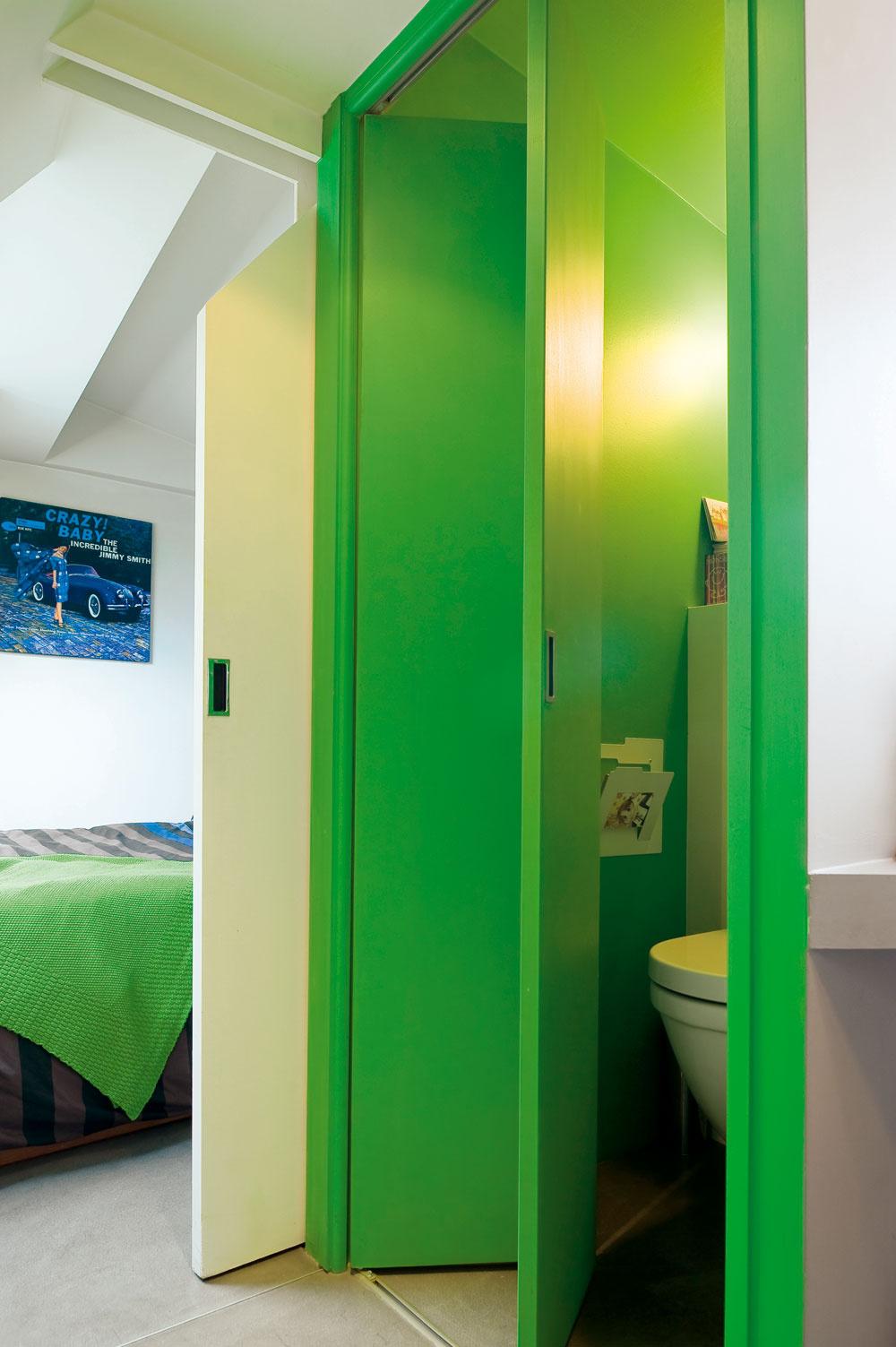 Hneď vedľa spálne je za zelenými skladacími dverami toaleta. Rovnako ako posuvné dvere spálne, prispôsobené sklonu strechy, sú aj dvere WC vyrobené na mieru. Aj vtomto prípade myslel architekt na to, ako čo najpraktickejšie využiť daný priestor. (Pletená prikrývka na posteli je od Zara Home.)