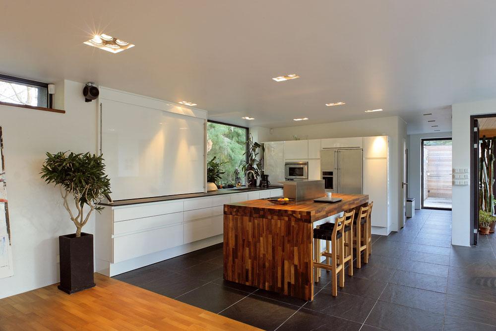 Kuchyňa SieMatic, lakovaná na lotosovú bielu, splýva so stenami, ostrov zorechového dreva je zladený spodlahou. Vedľa vstupu do zimnej záhrady vidieť chodbu zatáčajúcu doľava kvstupným dverám domu, cez okno na chodbe vidieť priestor pred hosťovským pavilónom, ktorý sa za pekného počasia využíva na stolovanie.