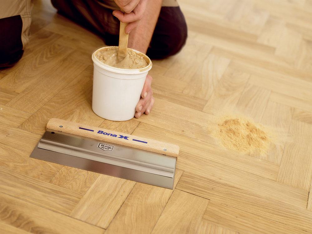 Pomocou antikorovej špachtle naneste na celú plochu miestnosti do škár podlahy tmel zmiešaný sbrúsnym prachom. Ten vyplní drobné nerovnosti vpodlahe. Po jeho vytvrdnutí – približne po 30 minútach – môžete začať sposledným brúsením. Pozor: Škáry vpodlahe zpalubovky sa neodporúča tmeliť!