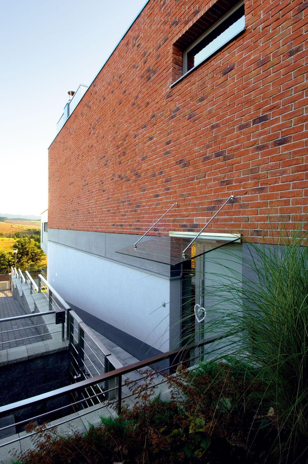 Použitie exteriérových stavebných materiálov je založené na vzájomnom farebnom apovrchovom kontraste. Pôsobivá je najmä kombinácia keramického obkladu so vzhľadom surovej tehly aantracitových obkladových fasádnych dosiek somietanou časťou prízemia. Moderná avýrazovo čistá architektúra domu sa pritom prispôsobila svahovitosti pozemku apolohe prístupovej cesty.