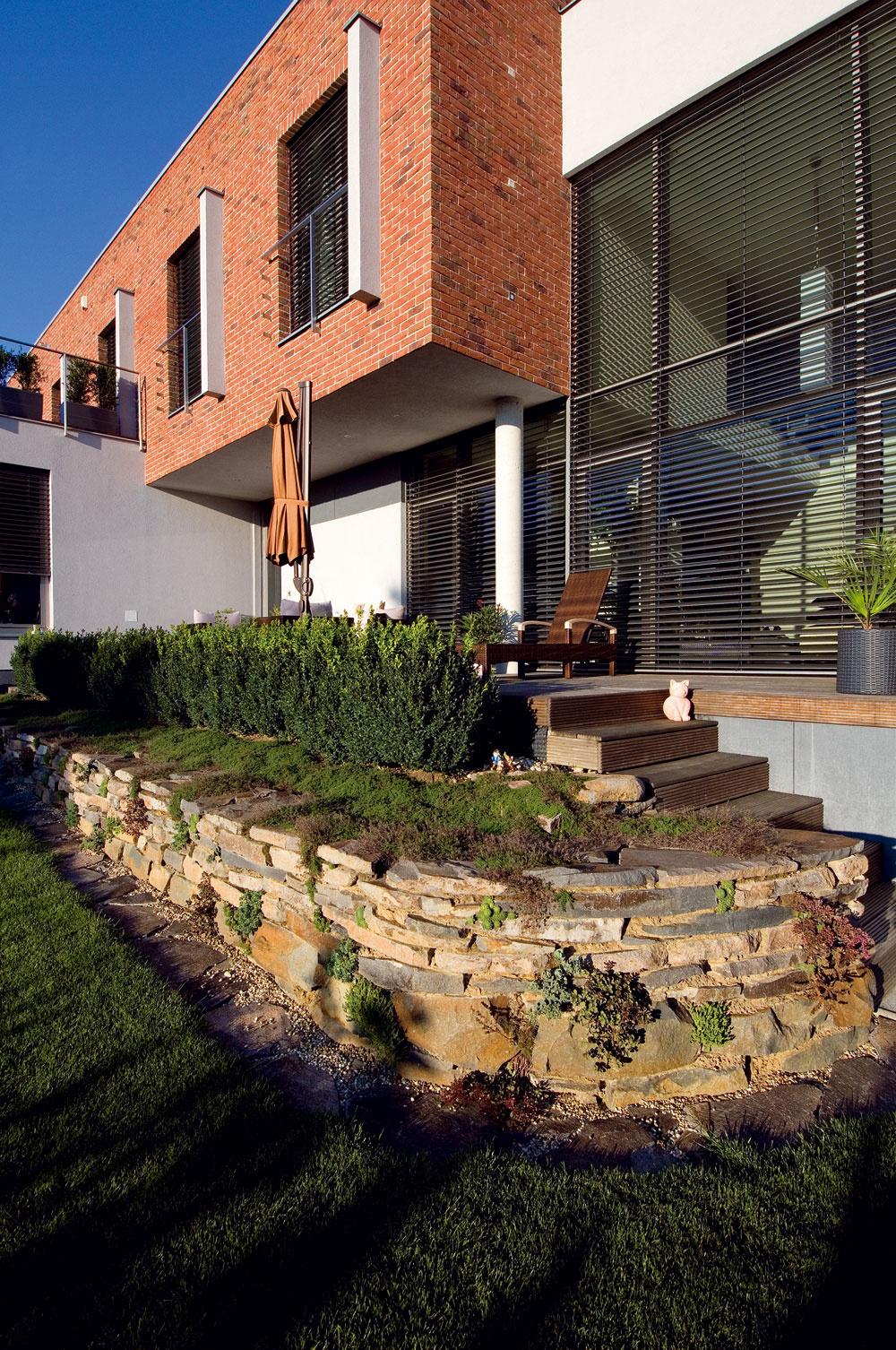 """Dom je citlivo osadený vteréne anapriek potrebným úpravám pozemku aj formou oporných múrov nepôsobí rušivo. """"Pozemok nám veľkosťou úplne vyhovuje, máme kúsok vlastnej zelene, ale nie sme otrokmi záhrady,"""" zhodujú sa majitelia. Ozáhradu navrhnutú architektom sa celoročne stará domáca pani azáhradnícka firma napráva škody spôsobené zimou."""