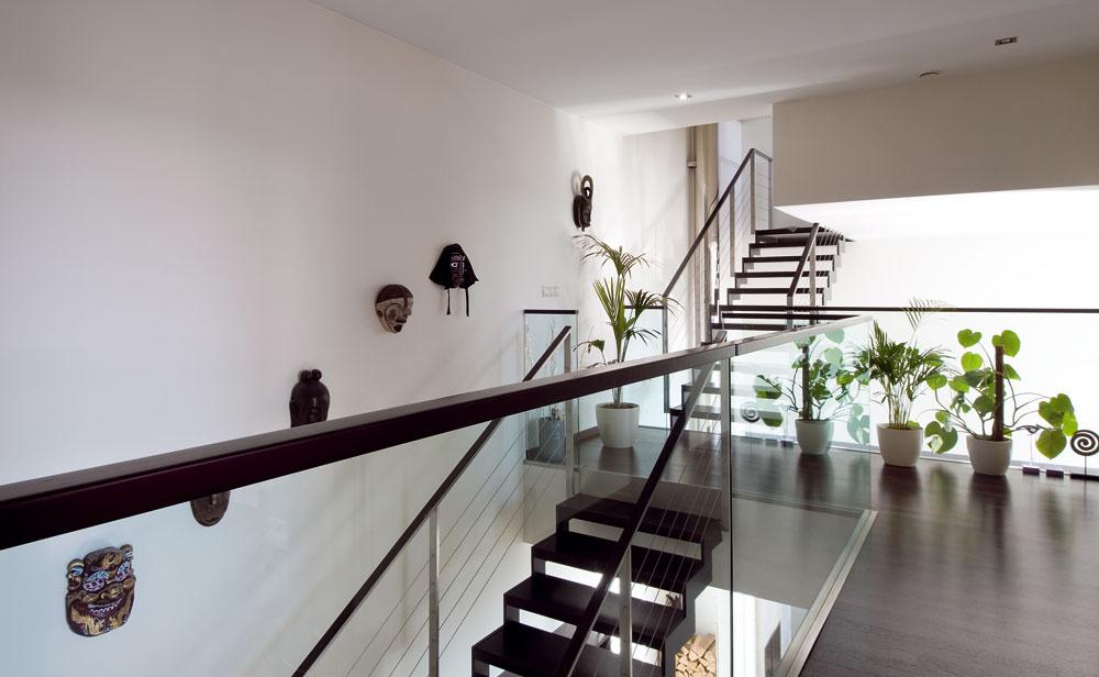 Nie každému vyhovuje otvorený pohľad zvýšky. Sklo tvoriace zábradlie na poschodí doplnili drevenými lištami, ktoré priestor zpocitového hľadiska vymedzí.