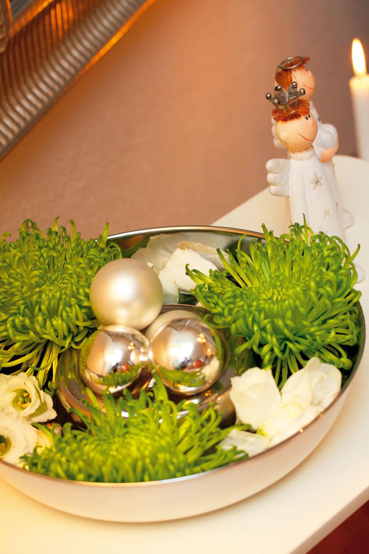 Dizajnová ikebana. Koncom roka kvitnú chryzantémy, prečo ich nevyužiť aj počas Vianoc? Do bielej misy so strieborným vnútrom dizajnérka naliala vodu. Do nej poukladala len kvety chryzantém abielych ruží, oboje bez stopiek. Do stredu, na vyvýšené dno, umiestnila zopár strieborných gulí. Dekoráciu dopĺňajú dvaja anjelici.