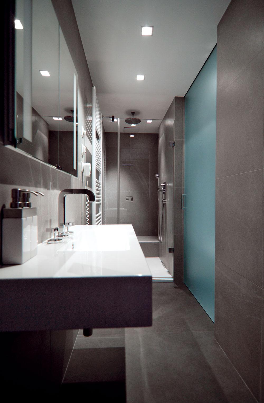 Kúpeľňa je úzka, preto bolo potrebné jej zariadenie riadne premyslieť. Toaleta na pravej strane je oddelená dverami zmliečneho skla, čo však zpraktického hľadiska nie je potrebné, keďže pripojenie na ventilátor zabezpečuje odsávanie pachov priamo zmisy.