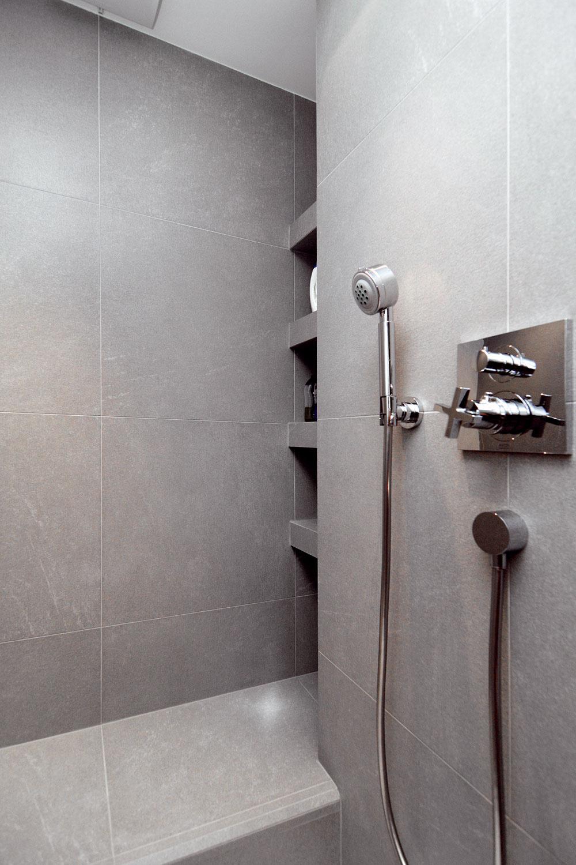 Úložné priestory na predmety každodennej potreby býva ťažké navrhnúť tak, aby boli poruke azároveň neviditeľné. Vkúpeľni to architekt dosiahol zapustením políc za úroveň steny tak, aby boli pri vstupe do kúpeľne neviditeľné, ale pri používaní sprchy ľahko dosiahnuteľné.