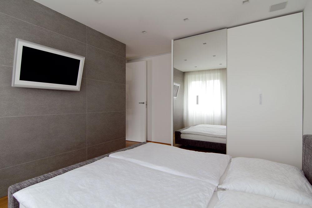 Veľkoformátový obklad na stene spálne dodáva miestnosti pocit chladu apokoja.