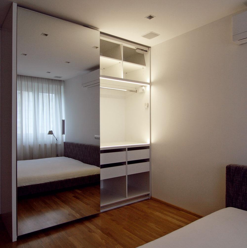 Biela skriňa vsebe ukrýva dostatok priestoru nielen na šaty, ale aj hifi systém. Zrkadlové dvere priestor spálne opticky zväčšujú.
