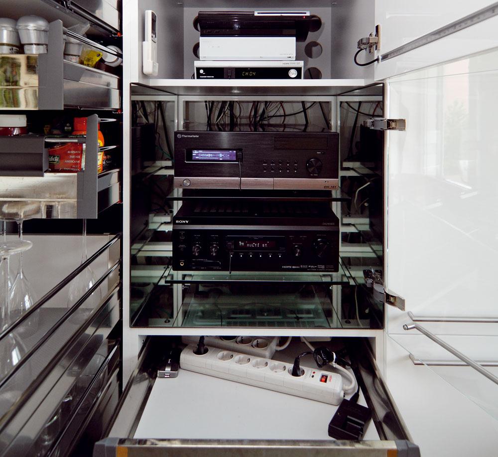 """Vrámci zachovania čistoty interiéru aochrany pred prachom umiestnili hifi komponenty, počítač aj tlačiareň do kuchynskej zostavy. """"Pekné komponenty"""" – počítač areceiver sú za sklenenými dverami na policiach zkaleného skla. Menej estetické, ale potrebné komponenty ako settop box, playstation atlačiareň ukryli za plné dvierka. Tieto skrinky nemajú zadné steny, čím sa dosiahlo optimálne prúdenie vzduchu za skrinkou aodvetrávanie zariadení."""