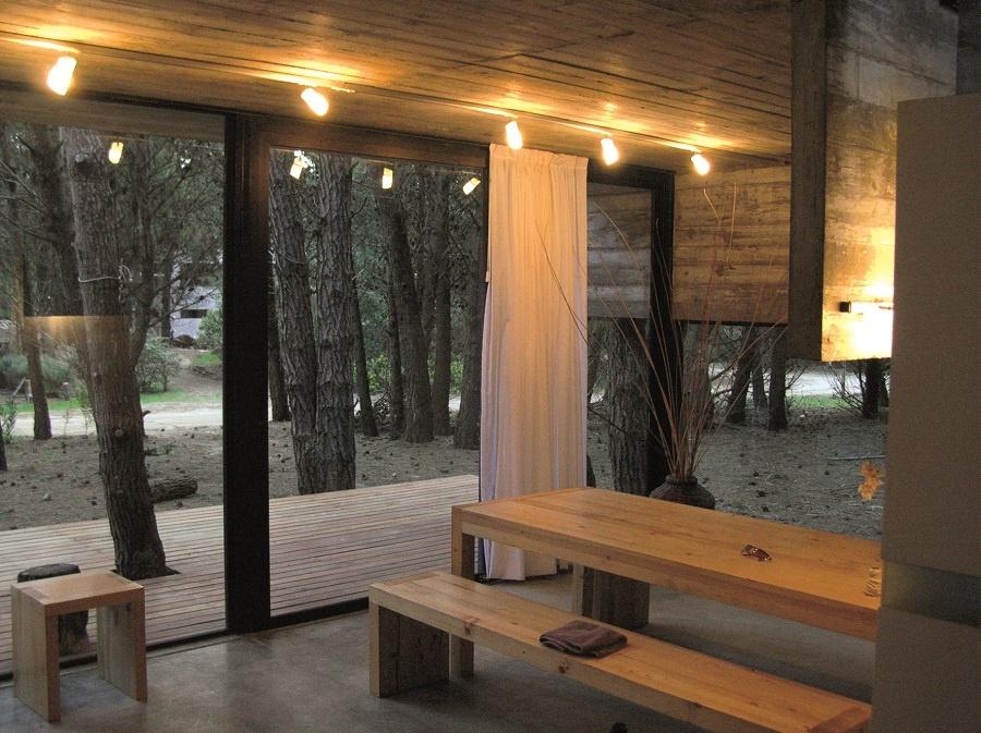 Skryť tvár príbytku do dlaní vetiev borovicovej aleje, kde kmeň stromu prerastá lesným domom a tento ho využíva ako svoj ochranný štít pred vetrom, dažďom, ale i slnkom. (foto: Besonias, Almeida, Kruk Arquitectos)
