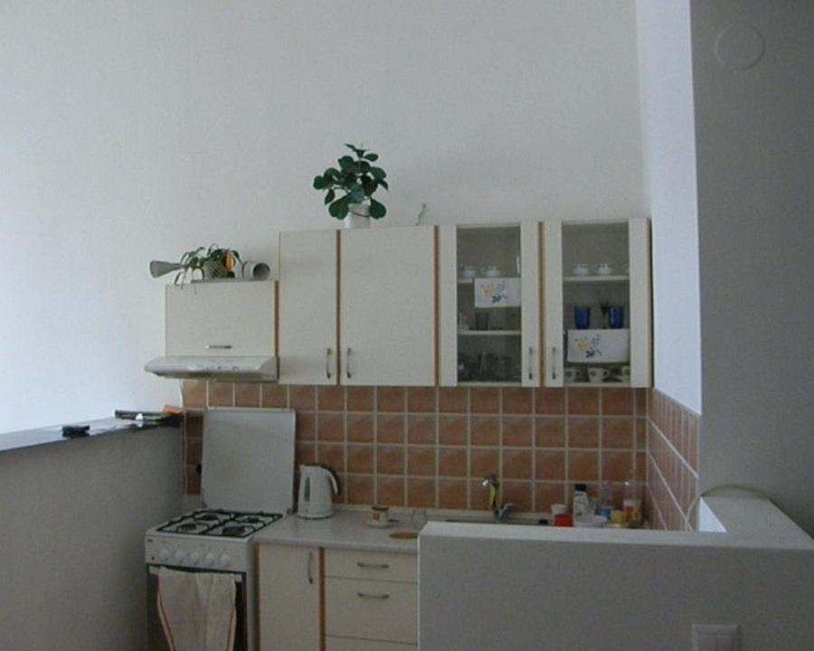 Predtým: Sterilná malá kuchyňa pôsobí bez farebných prvkov ako bez života. Ohraničená bielymi polpriečkami vyvoláva pocit chladu a izolácie od ostatnej časti priestoru. (foto: Lucia Pristachová Hô-Chí)