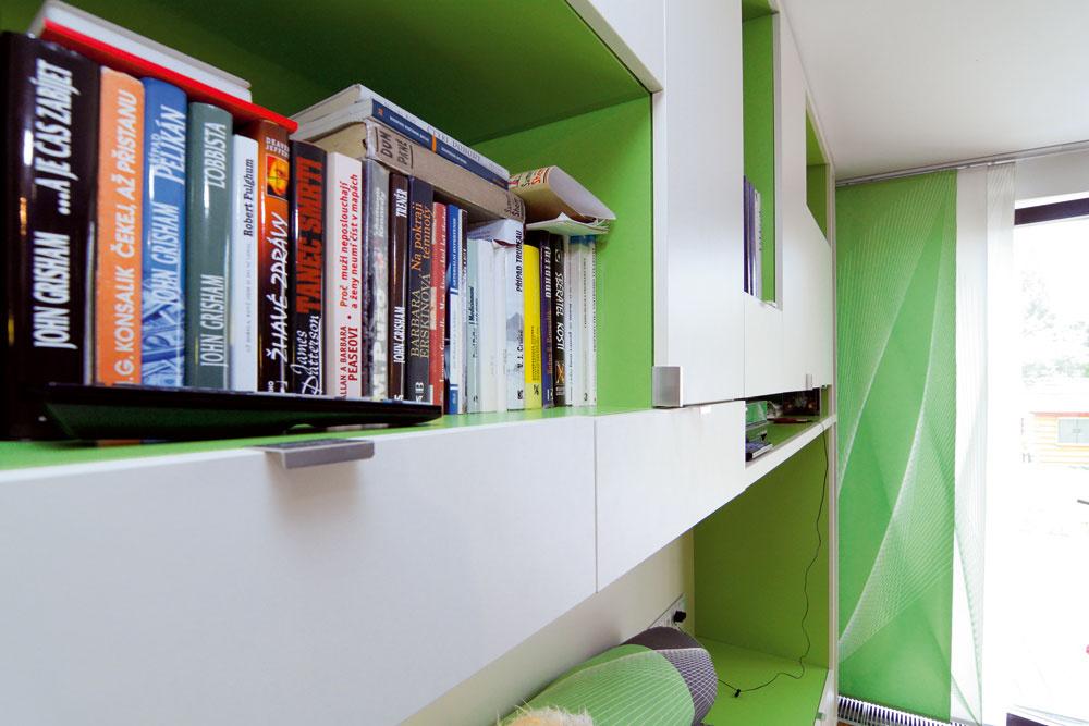 Skriňová zostava pôsobí vzdušne aľahko. Prispieva ktomu dynamické striedanie zelenej abielej farby aotvorených regálov splochami.