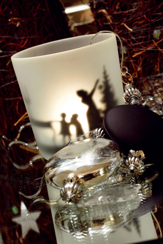 Svietnik X-mas zmliečneho skla od firmy Leonardo, 9 cm, cena 9,15 €. Závesné ozdoby od firmy Boltze, strieborné ačierne, 19 cm, cena 9,30 €/ 2 ks. Predáva Galan.