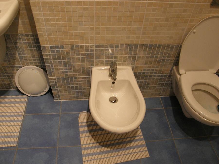 Predtým: S ľadom a skladom vyzerala kúpeľňa na začiatku. Modrá podlaha napriek oranžovej mozaike na stenách pôsobí chladne a roztrúsené zbytočnosti po zemi zas skladne. (foto: Lucia Pristachová Hô-Chí)