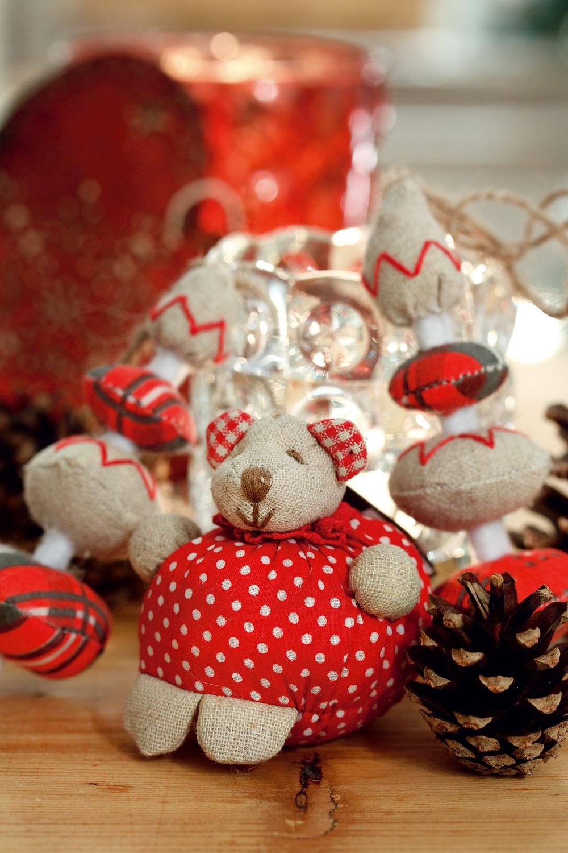 Textilná ozdoba Meda od firmy Sia, 6 cm, 4,90 €. Vpozadí červené drevené srdce Heidi so zlatým ornamentom od firmy Boltze, 12 cm, cena 3,63 €. Predáva Design House aGalan. Svietnik Yrsnö zčíreho skla, 8 cm, cena 1,49 €. Závesná dekorácia Yrsnö vtvare stromčeka zbavlny, ľanu ajuty, 11 cm, cena 5,99 €/4 ks. Predáva IKEA.
