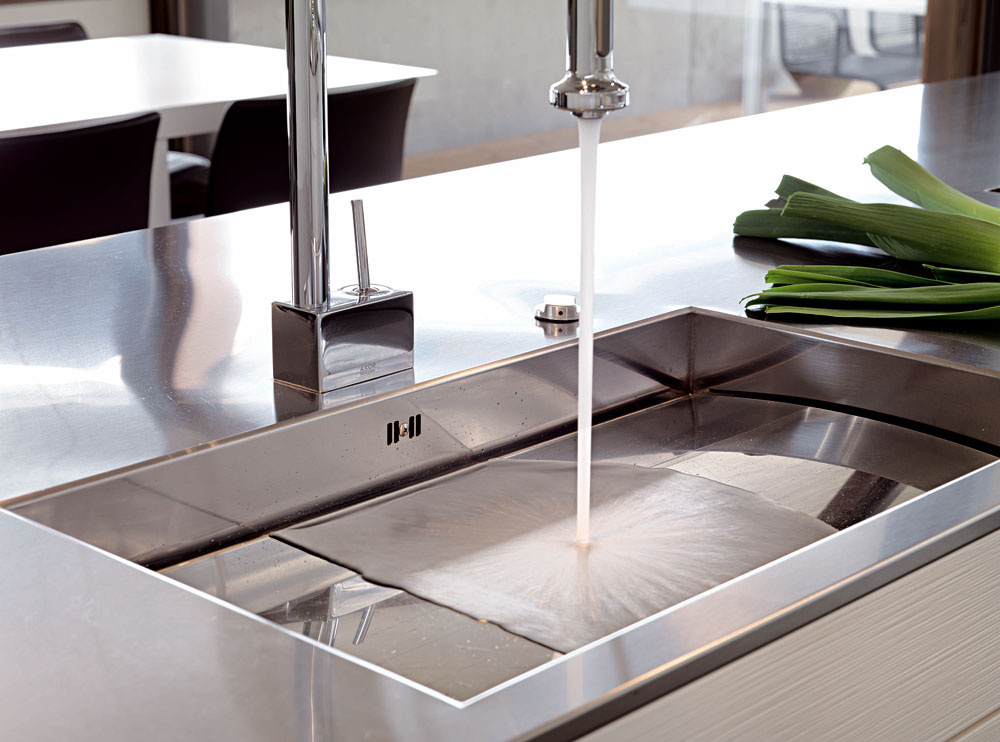 Ak máte vysoké požiadavky na dizajn každého detailu vdomácnosti, môžete si dať vyrobiť kuchynský drez aj na mieru. Nezabudnite však na funkčnosť, pretože dizajn pre dizajn vám skomplikuje každodenné činnosti. Napríklad vo firme Leicht vyrobili tento drez, ktorý má zaujímavo riešený odtok – cez okrajovú štrbinu, no nezabudli na to, že voda by bez pridávania vzduchu vkohútiku fŕkala na všetky strany, keďže dopadá na rovnú plochu. Takto po nej pekne kĺže.