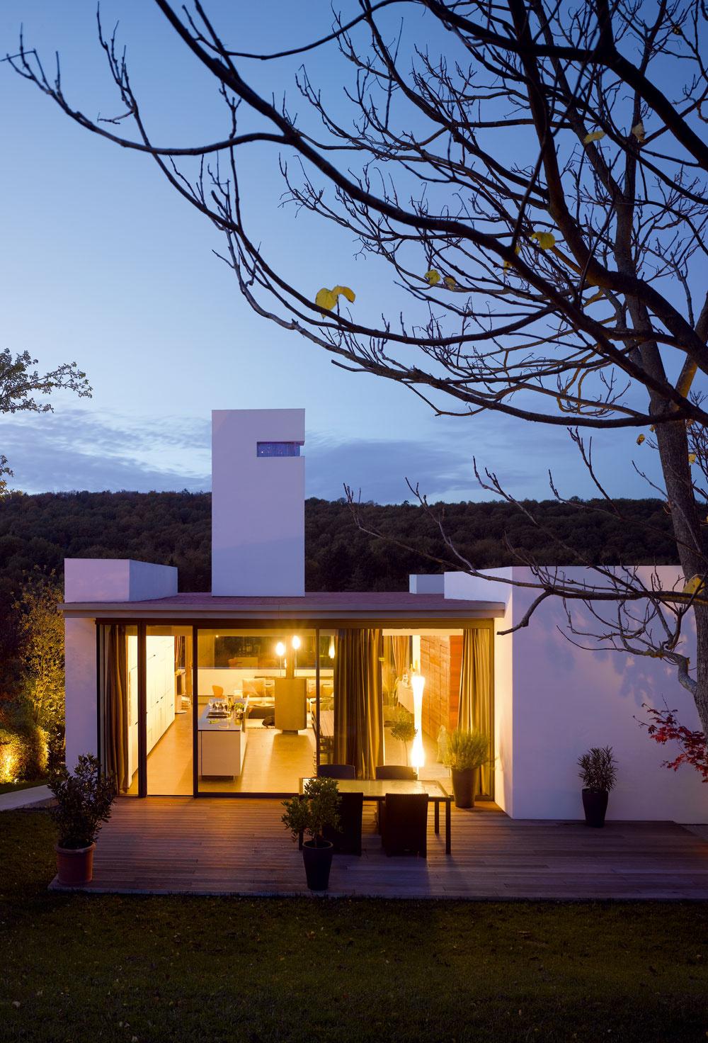 Po zotmení žiaria do noci nielen veľké okná, atmosféru vytvárajú aj podsvietené rastliny. Ako vidieť na ľavom okraji snímky, bodové svetlá smerujú na elegantné javory aj na skromnejšie kry. Pointou sú svetielkujúce LED diódy vo výreze komína, čo je vraj signál, že majitelia sú doma.