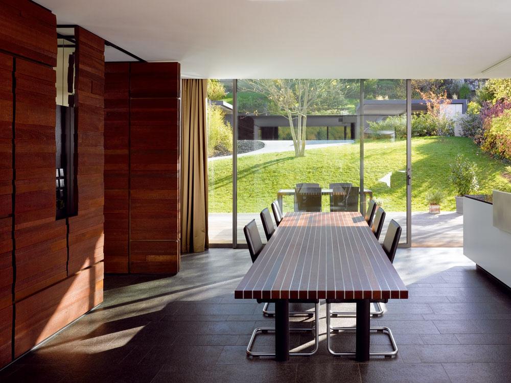 Celé zariadenie okrem sedacieho ačalúneného nábytku navrhol ateliér Alexandra Brennera: na snímke je sústava skriniek, jedálenský stôl zjatobových dosiek prekladaných hliníkovými pásmi aj kuchynský ostrov spracovnou plochou zčiernej zimbabwianskej žuly nero assoluto ashliníkovou doskou. Tak ako ostatné materiály, aj kov vinteriéri vily nadväzuje na vonkajšie kovové prvky – oceľové zakončenie strechy adetaily zpráškovo lakovaného hliníka na parapete balkónu.