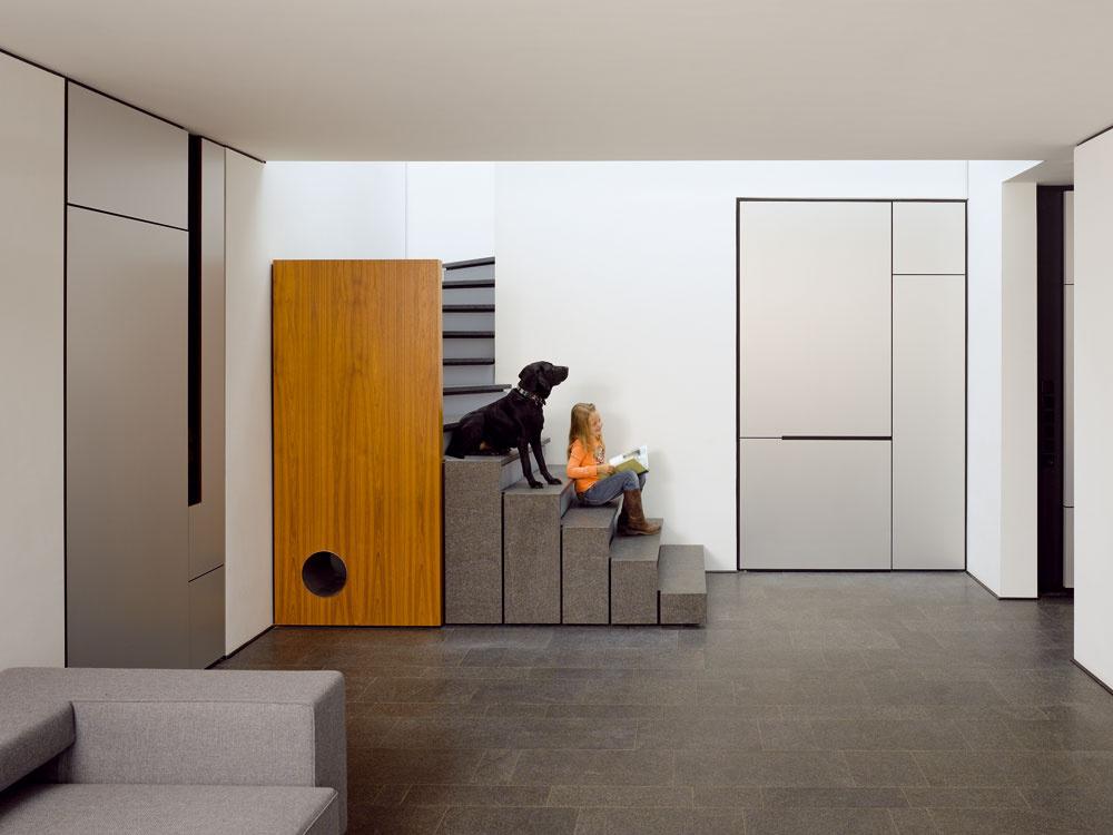 Schody sbariérou ztíkovej dosky ústia do herne – spodnej obývačky, odkiaľ sa otvorom pri pravom okraji snímky vchádza chodbou do detských izieb. Po oboch stranách schodišťa sú vstupy sdverami vštýle kuchynských skriniek, ľavé dvere vedú cez chodbu do hosťovskej izby, tie vpravo do sauny.  Pohovka je zrovnakého modelového radu Andy od Paola Pivu (B&B Italia, 2002) ako sedačka vobývacom priestore. Za oknom je vo vrstve sivého drveného kameňa, ktorý farebne komunikuje sdlažbou herne, vysadený javor dlaňovitolistý 'Blood Good, jeden zviacerých náznakov inšpirácie Ďalekým východom.