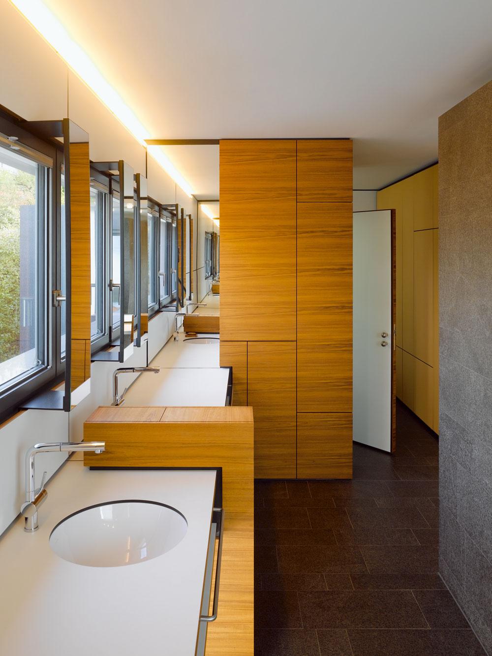 Vkúpeľni pri spálni rodičov spásovým oknom, ktorým ráno príjemne prenikajú slnečné lúče, upúta tíkové drevo nábytku. Pootvorené dvere prikrývajú priestor, ktorý majitelia využívajú ako malú pracovňu. Vpravo je deliaca stena sprchy sbazaltovým obkladom, rovnakým ako na dlažbách vcelom dome.