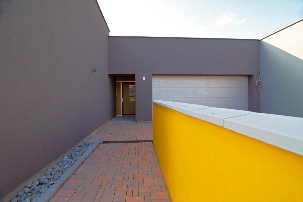 Jednoduchosť až strohosť moderného priedomia vtomto prípade osviežuje žiarivá žltá na múriku, ktorý sprevádza prichádzajúceho. Zapustené vstupné dvere vytvárajú pocit bezpečia. Trocha prírodnej zelenej, ktorá je tam asi aj plánovaná, by pridalo atmosféru. Ale inak veľmi moderné. (autor: Ing. Marek Ranocha)
