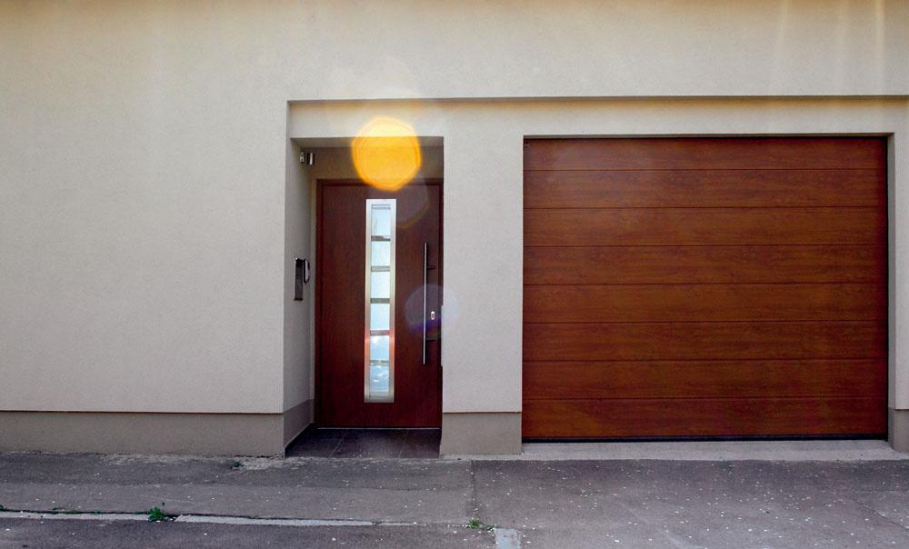 Ďalší príklad jednoduchého vkusu založeného na kvalitných materiáloch sdopracovanými detailmi. Ukážka toho, keď menej je viac. Malý nápad: farebne odlíšená ustupujúca časť okolo dverí agarážovej brány – tmavosivá alebo pokojne aj čierna by boli zaujímavé.