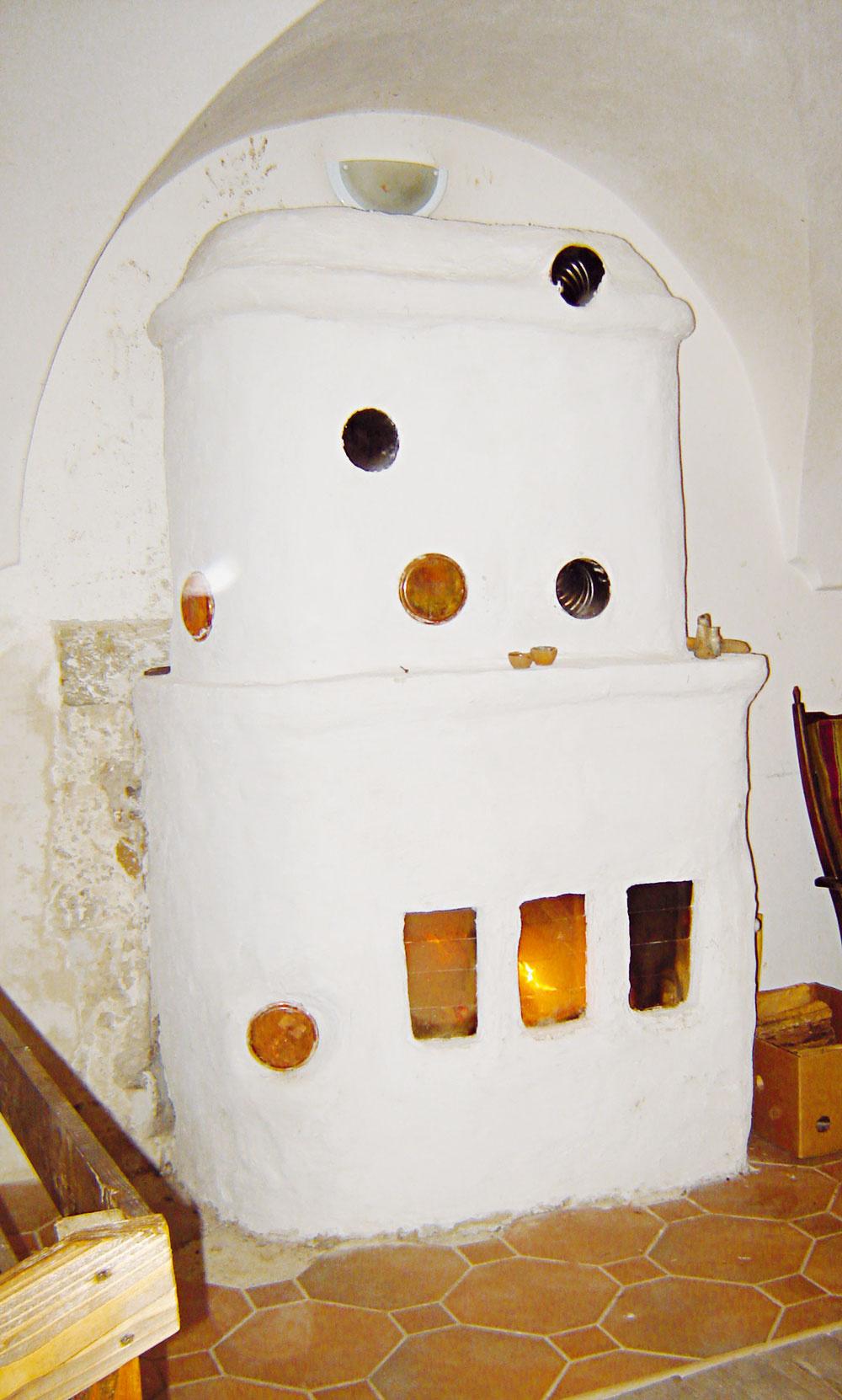 Pec znepálených tehál Pec je postavená zväčšej časti znepálených hlinených tehál. Len ohnisko aprvý ťah sú chránené šamotovými tehlami proti mechanickému poškodeniu. Pec má štyri zvislé ťahy ajeden vodorovný. Posledný ťah je až ku dnu ohniska, lebo sa použil pôvodný komín vpamiatkovo chránenom objekte, kde sa nemohli vykonať žiadne nezvratné stavebné úpravy, ani búranie nového otvoru do komína. Vrstva omietky je oddilatovaná skleneným pletivom, zavesená na kovovom pletive. Hlinená omietka vo viacerých vrstvách je spevnená sekaným skleneným vláknom anapustená vápenným pačokom.