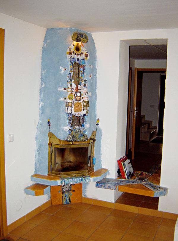 """Modrá pec Obvyklá kozubová vložka je obložená mosadzným plechom, vložka je uložená na betónovú konzolu. Docielila sa ľahkosť avoľnosť priestoru. Počas rekonštrukcie sa našli vmiestnosti zamurované dvere. Boli opäť otvorené avyužité na """"zavzdušnenie"""" priestoru. Polička znemožňuje neželaný priechod. Kvyváženiu kompozície bol využitý aj menší prvok vľavo. Modrá farba pece postupne prechádza do bielej. Pec nie je presne ohraničená, oddelená od steny. Docielil sa efekt potupného prechodu pec – stena. Na peci je inštalovaná demontovateľná, perforovaná plastika, ktorá slúži aj ako mriežka vzduchotechniky. (realizácia: autor, 2005)"""