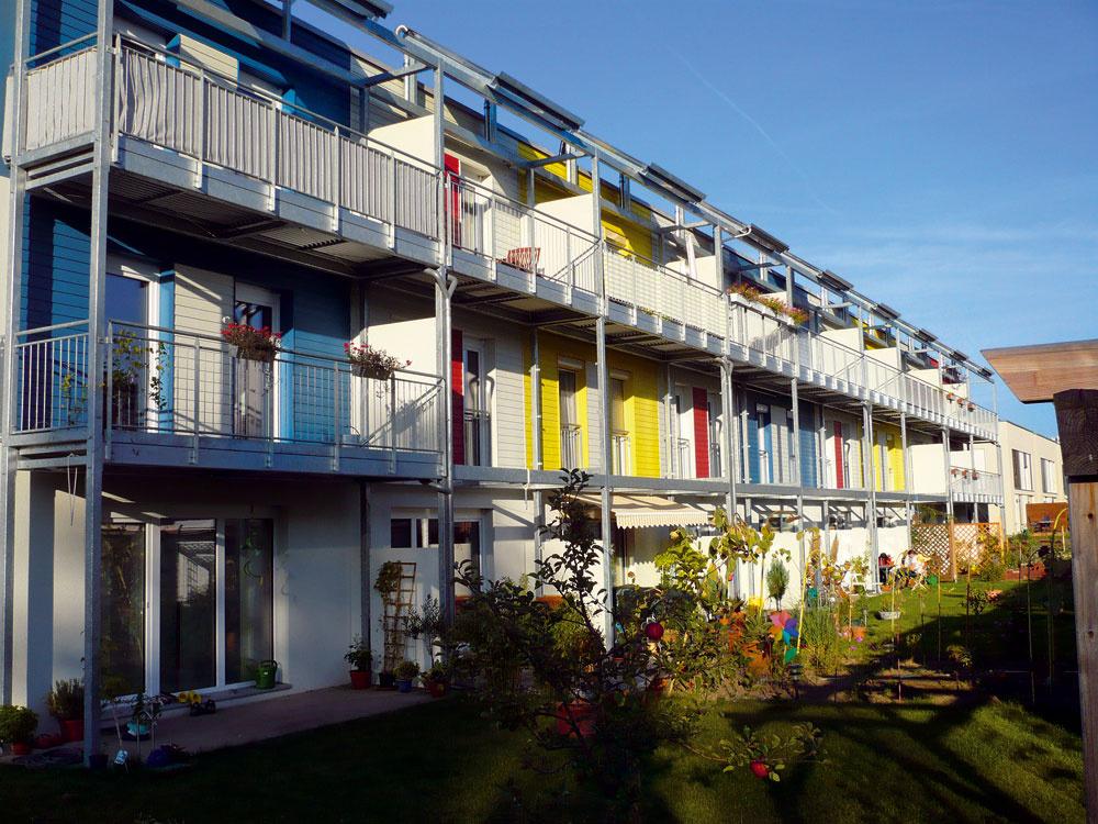 Radové pasívne domy vKarnichsteine (Nemecko). Južné zasklenia sú tienené predsadenými konštrukciami balkónov asolárnymi kolektormi.