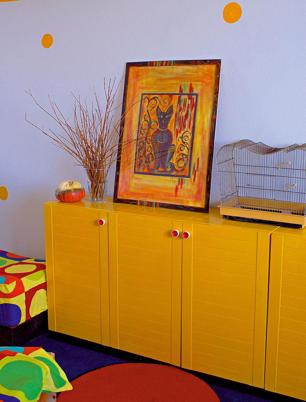 Staré skrinky sa oživili žltým syntetickým náterom na drevo. Na nich si teraz hovie obraz orientálnej mačky. Geometria sa ztextílií preniesla aj na steny – farebné akrylové kruhy sa striedajú so štvorcami.