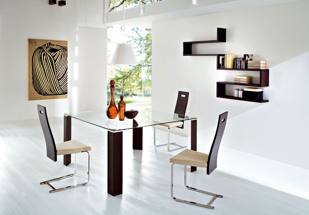 Stôl Dylan sdrevenými nohami morenými na čerešňu awenge alebo snohami obtiahnutými regenerovanou kožou. Doska stola je ztransparentného skla. Vložky nôh pod sklom sú zhliníka, cena 630,80 €, predáva www.italiastyle.sk.