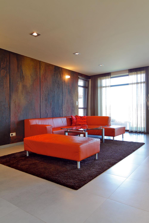 Celý spoločenský priestor je vyriešený veľmi veľkoryso anapriek prvému dojmu, že ide omalý dom, interiér prekvapí svojou rozlohou. Pohľad upúta stena snetradičnou povrchovou úpravou, ale aj priestranná sedacia súprava, ktorá akoby pozývala urobiť si pohodlie. Obývačka momentálne plní hlavne funkciu detského ihrisk