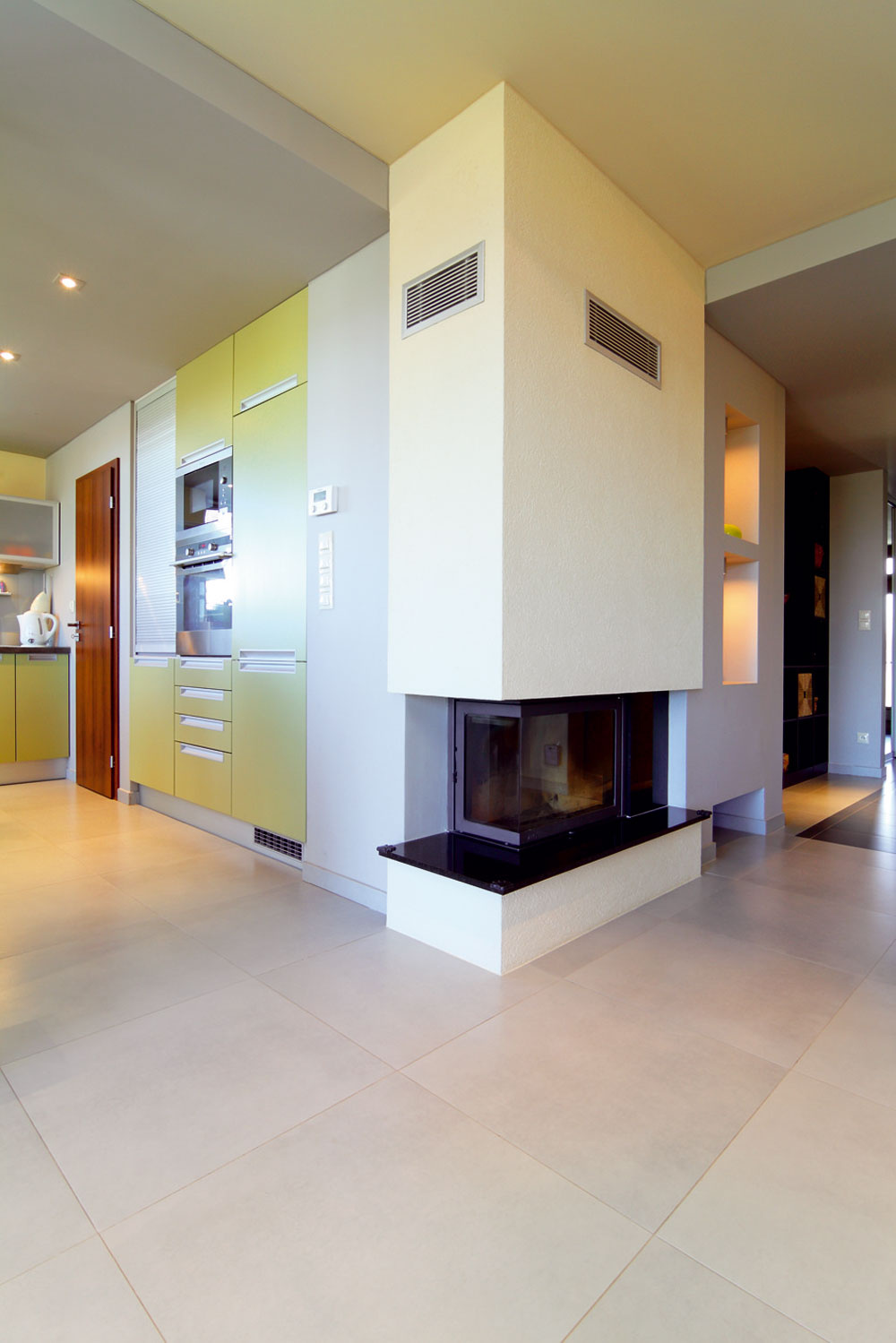Obývacia izba plynule prechádza cez presne nedefinovanú halu do priestrannej kuchyne smiestom na stolovanie. Pocit plynulosti umocňuje veľkoformátová dlažba, ktorá pokrýva celú spoločenskú časť domu.