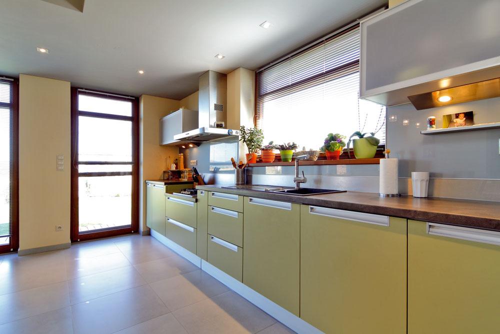 Pri 5 metrov dlhej kuchynskej linke nemôže byť ani reč onedostatku odkladacieho priestoru. Možno práve preto pôsobí kuchyňa včase mimo prevádzky, ako keby sa ani nepoužívala. Všetko sa totiž dá bez problémov odložiť. Nižšie položená varná doska berie ohľad na výšku domácej panej, ktorá oceňuje, že po varení nemusí čistiť široké aďaleké okolie, ale iba bočné steny priľahlých skriniek, aže východné slniečko dodáva pri ranných kuchynských rituáloch optimizmus.