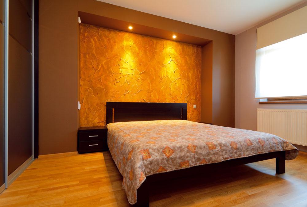 Spálňa je celá ladená do hneda. Dominantne pôsobí stena za čelom manželskej postele, ktorú vytvorili postupným farebným tónovaním nahrubo nanesenej sadrovej omietky.