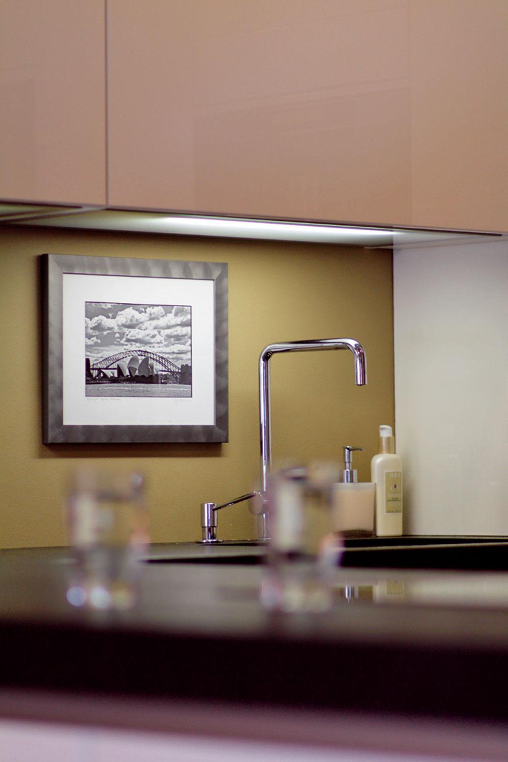 Továrenský pôvod sa tomuto interiéru jednoducho nedá odoprieť aprejavuje sa aj vmnožstve doplnkov. Priestor za kuchynskou batériou je zjemnený obľúbeným motívom majiteľky – čiernobielou fotografiou.