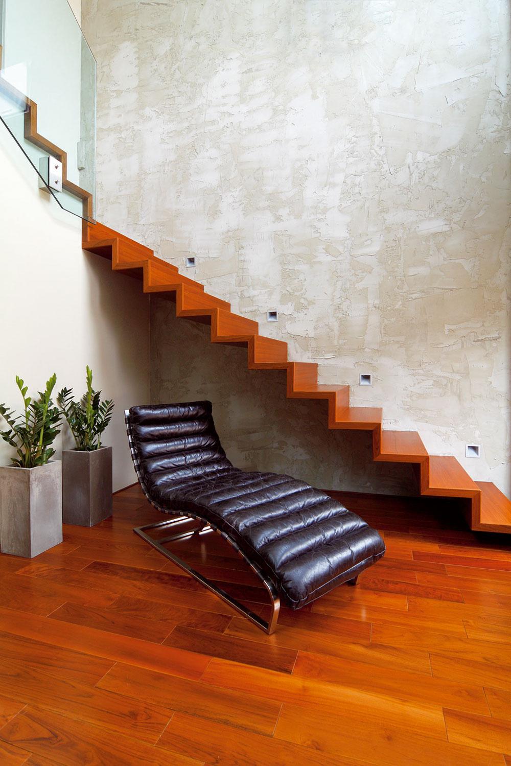 """Pekne vydarené zátišie, v ktorom hlavnú úlohu hrá dizajnový kožený diván, ľahučká konštrukcia schodiska a továrensky """"rozleptaná """" stena."""