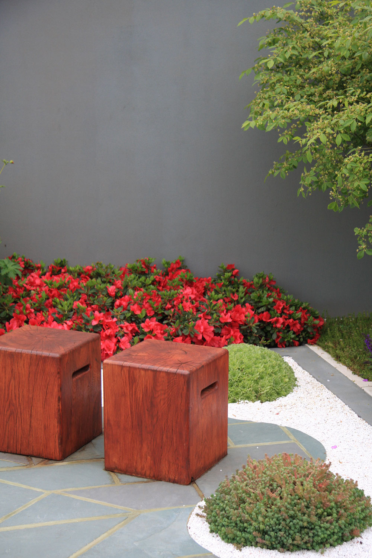 Ďalším zmateriálov je popri kameni akove drevo, ktoré sa tu uplatnilo vpodobe záhradného nábytku. Drevené kocky na sedenie výborne zapadajú do celkového konceptu tejto strešnej záhrady azároveň ukrývajú malé úložné priestory.