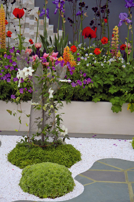 Oporu pre kvitnúci plamienok poskytla netradičná drôtená plastika. Stojí akoby na malom zelenom ostrovčeku – táto symbolika je prítomná vcelom záhradnom priestore.