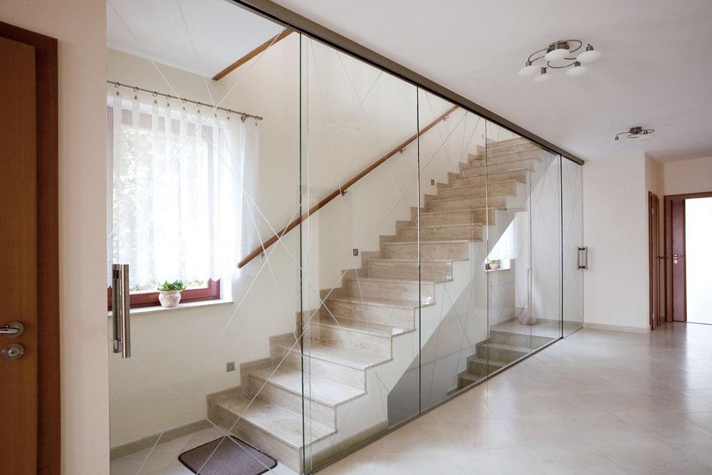 Schodisko môže byť peknou stavebnou konštrukciou, ktorú je škoda schovávať za plnú stenu. Sklenená priečka sposuvnými dverami avypieskovanými atypickými vzormi priestor rozjasní, oddelí aj spojí zároveň.