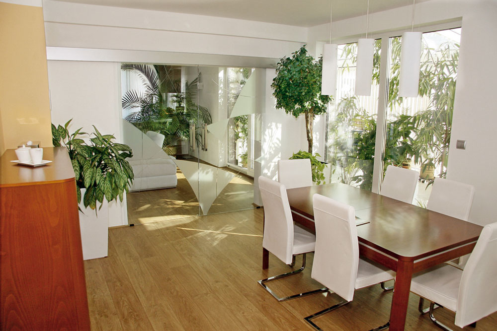 Sklenené bezrámové posuvné dvere pohybujúce sa popred stenu oddelia aj spoja jedáleň aobývačku.