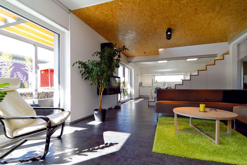 """Dominantným prvkom stropu obývačky je lakovaná drevoštiepková doska. Majiteľovi sa páči myšlienka """"priznaných"""" materiálov ako pohľadový betón či surová tehla. Obklady ztzv. OSB dosiek pôvodne chcel použiť aj vexteriéri, no pre poveternostné podmienky by nemali dlhú životnosť."""