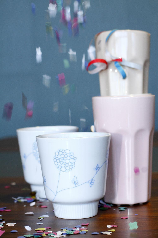 Dvojstenné keramické hrnčeky Bakelse sjemnými modrými kvetmi, vnútri udržiavajú tekutinu teplú, zvonka sú studené. Objem 24 cl, cena 3,99 €. Vysoké kameninové hrnčeky Pokal vpastelových farbách. Objem 4 dcl, cena 1,29 €. Predáva IKEA.