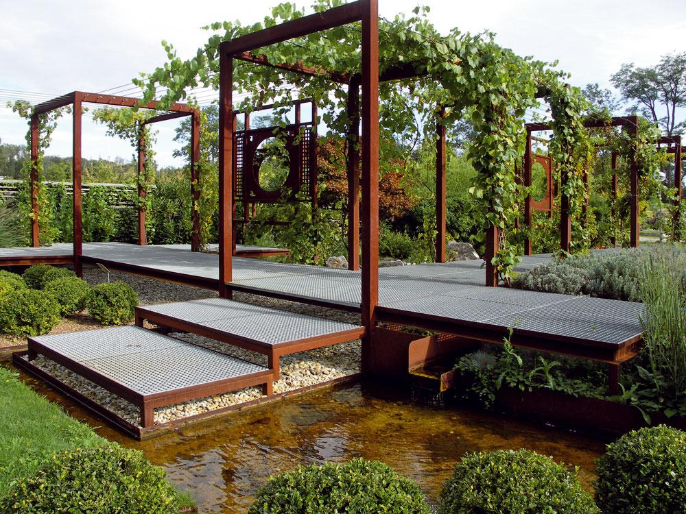 Necelé tri roky po založení ukážkovej záhrady vTullne už vnej vinič úspešne obrastá odvážne hrdzavé pergoly. Pod pergolami sa prechádza po zvýšenom chodníku, ktorého rošty sú ako jediný kov vtejto expozícii upravené pozinkovaním.