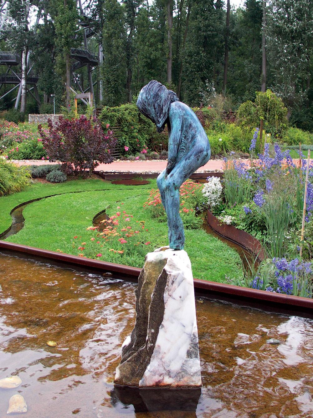 Po celej dĺžke jedného zchodníkov je vyvýšená kovová nádrž, ktorú pôvabne zdobí socha dievčaťa na vápencovom kameni. Hladina tejto veľkej nádrže je najvyššie, voda znej vyteká do kovových kanálov apreteká celou záhradou.