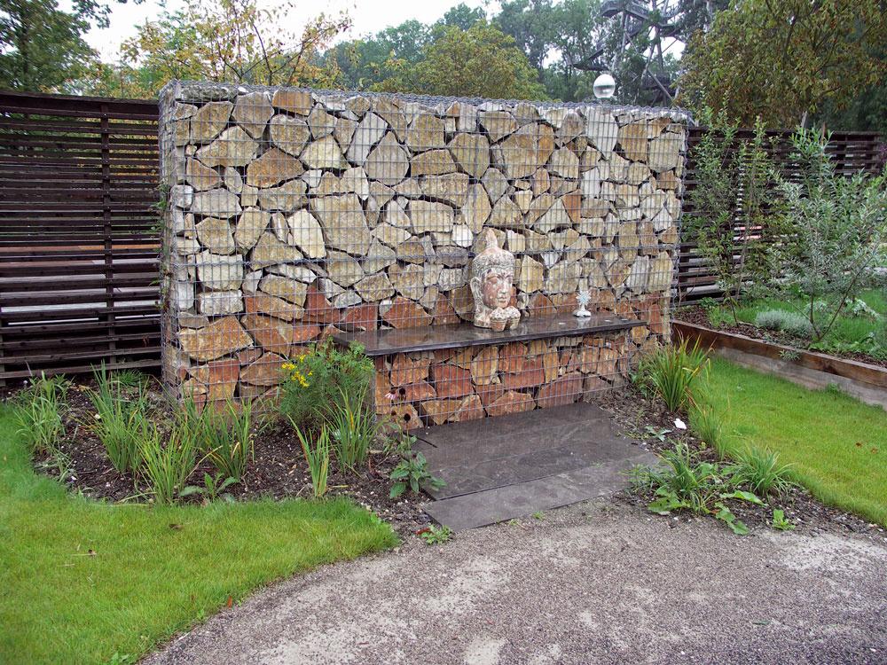 Gabiónová stena vyplnená mohutnými kameňmi slúži ako kulisa azároveň časť plota. Takáto úprava je vhodná skôr do väčšej záhrady. Nemusí však byť príjemná každému – asi najmä na dámy nebude pôsobiť práve útulným dojmom.
