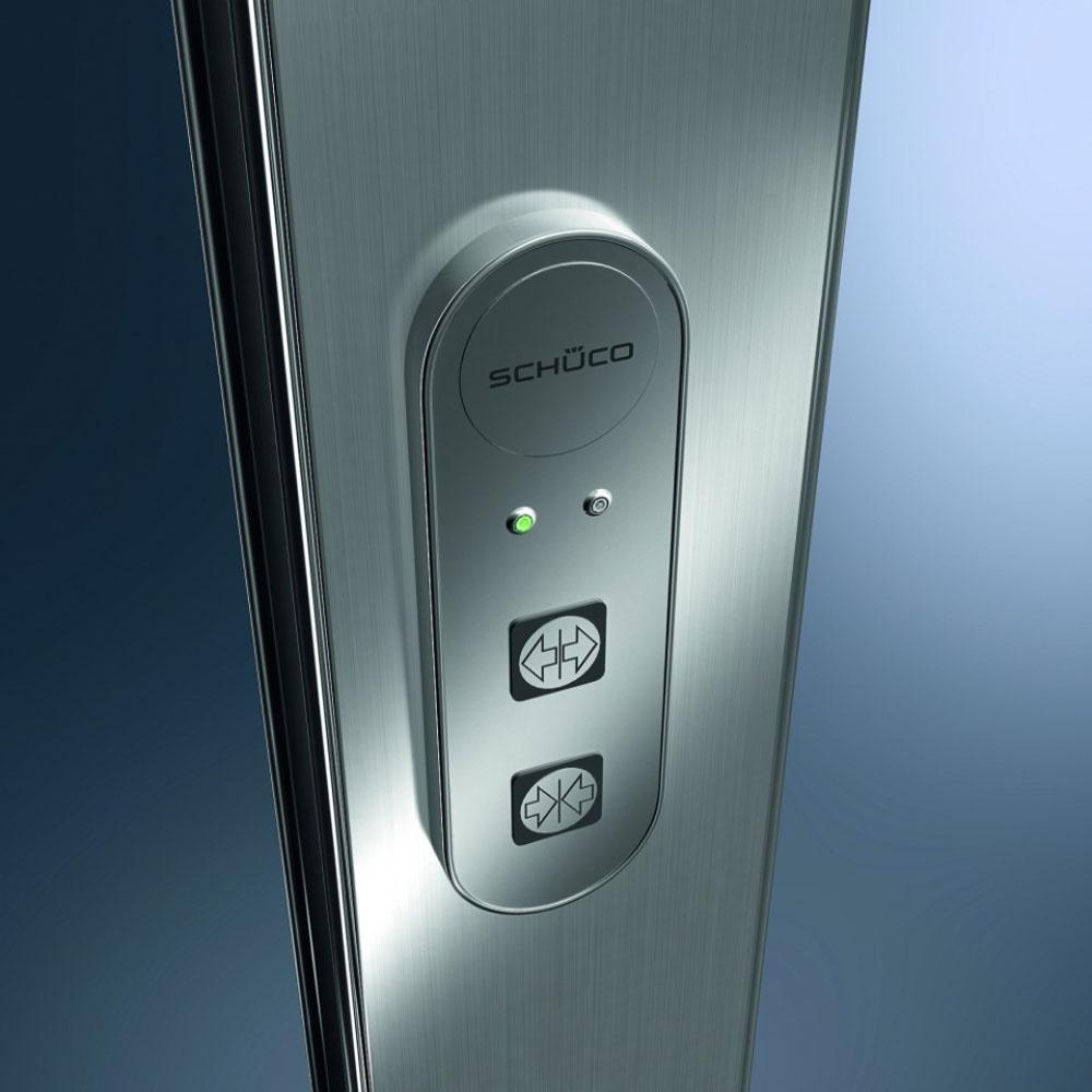 E-slide je alternatívne mechatronické kovanie na posuvné systémy značky Schüco, vďaka ktorému sa dajú aj rozmerné aťažké sklenené dvere ovládať ľahko apohodlne. Aby prístup zvonka bol naozaj bezpečný, možno ho vybaviť čítačkou odtlačkov prstov či kódovaním.