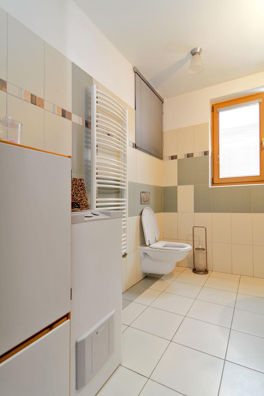 Kúpeľňa mala byť v  pôvodnom projekte podľa architektonického návrhu oveľa menšia, umývadlo sa malo ocitnúť pod oknom, na tej istej stene aj WC. Zmenili sme to na praktickejšie usporiadanie, a  najmä sme chceli väčšiu kúpeľňu, ktorá v  novšej verzii odkrojila z  pôdorysu vstupnej chodby do nášho bytu. Pre kotol a  zásobník vody sme tak mohli nájsť výhodnejšiu polohu.