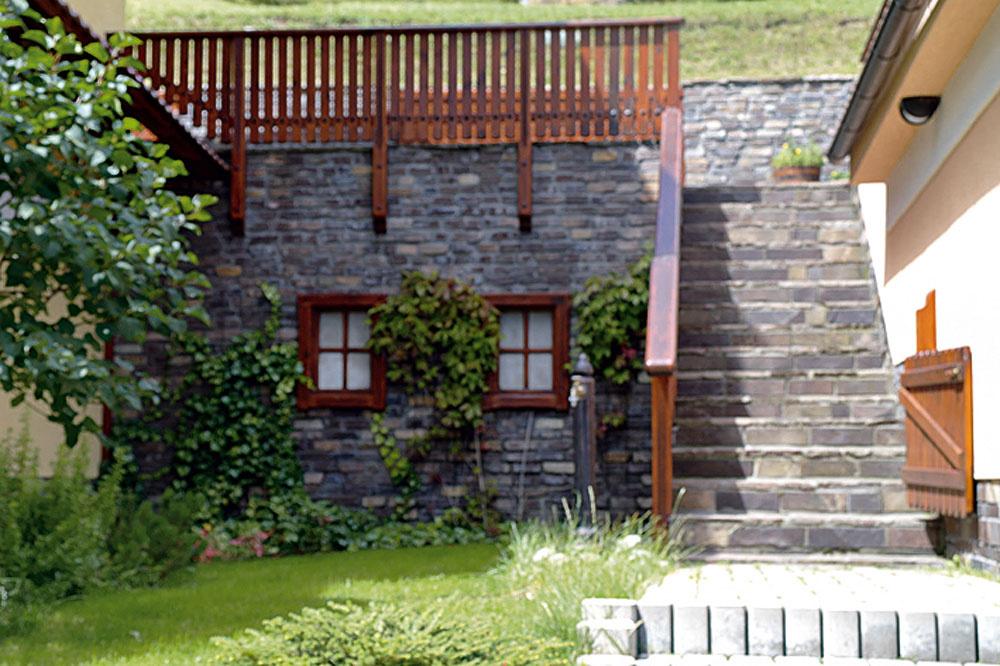 """Tu vznikli aj pri pomerne vysokých oporných múroch ozaj príjemné zákutia. Okrem popínavej zelene im prospeli aj drevené detaily aschody, ktoré ich pekne rozčlenili, atiež milá drobnosť – slepé okienka, respektíve dvere. Veď vtakomto romantickom prostredí celkom dobre padne trocha toho """"sladkého""""."""