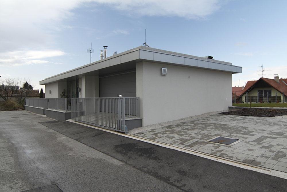 Zo strany ulice je priznaná len subtílna jednopodlažná vstupná časť do domu, hoci konštrukcia pokračuje smerom nadol. Vpravo vidieť predchádzajúci dom majiteľov.